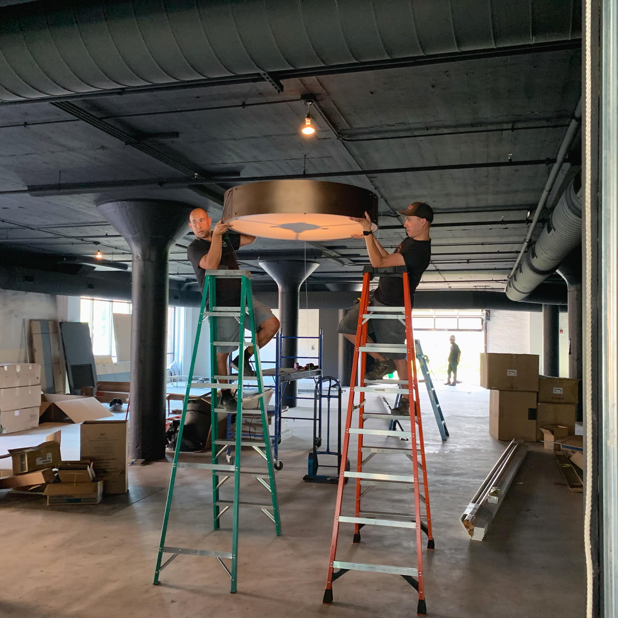 Hogan workers mount round lighting fixture in commercial project
