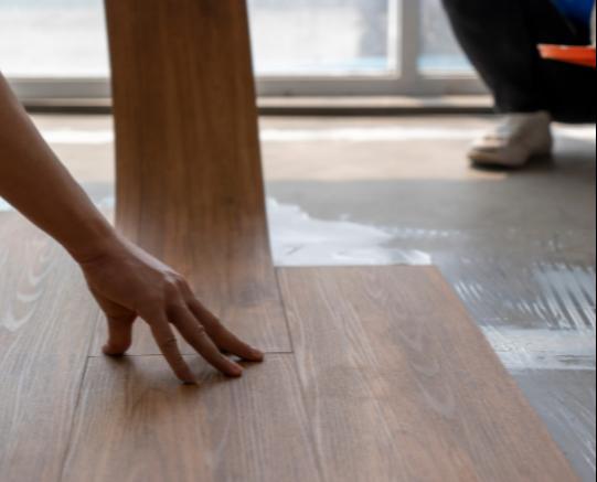 Carpenter laying vinyl flooring in new home