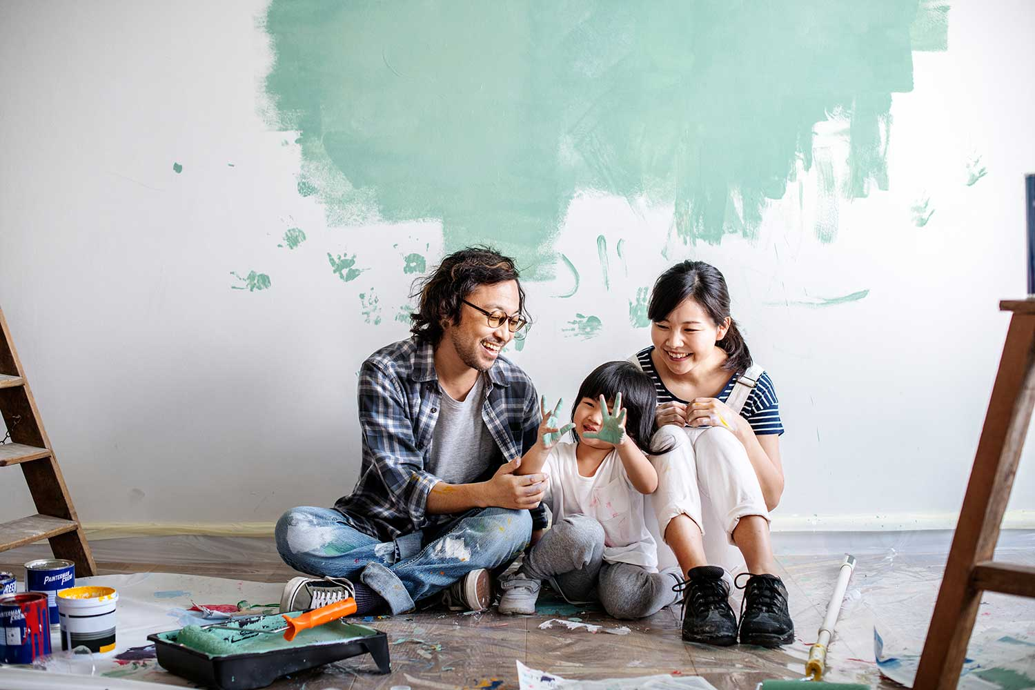 Two people sit on green and white wall picking colors