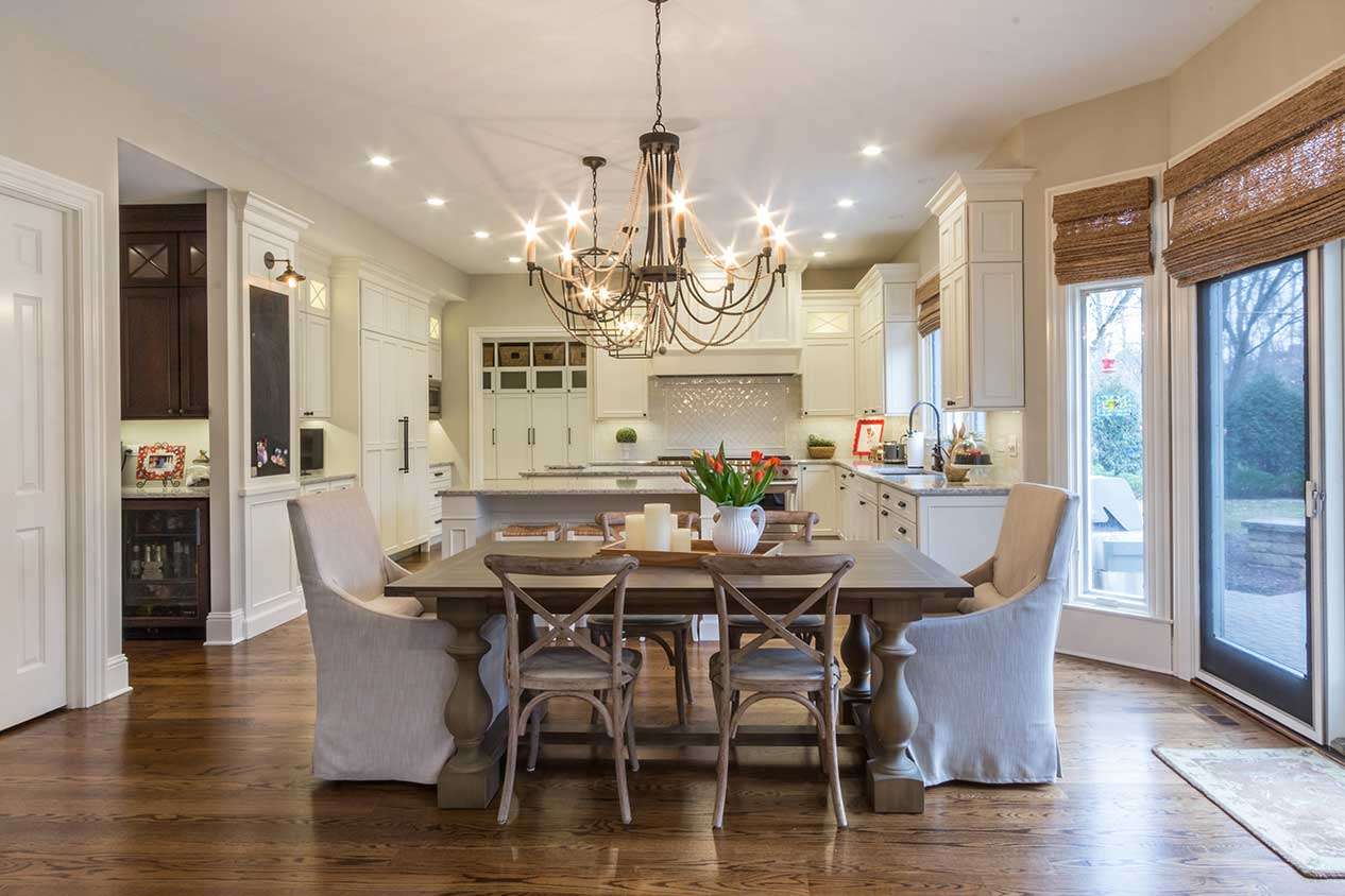 Dining table with bronze chandelier and white cabinets