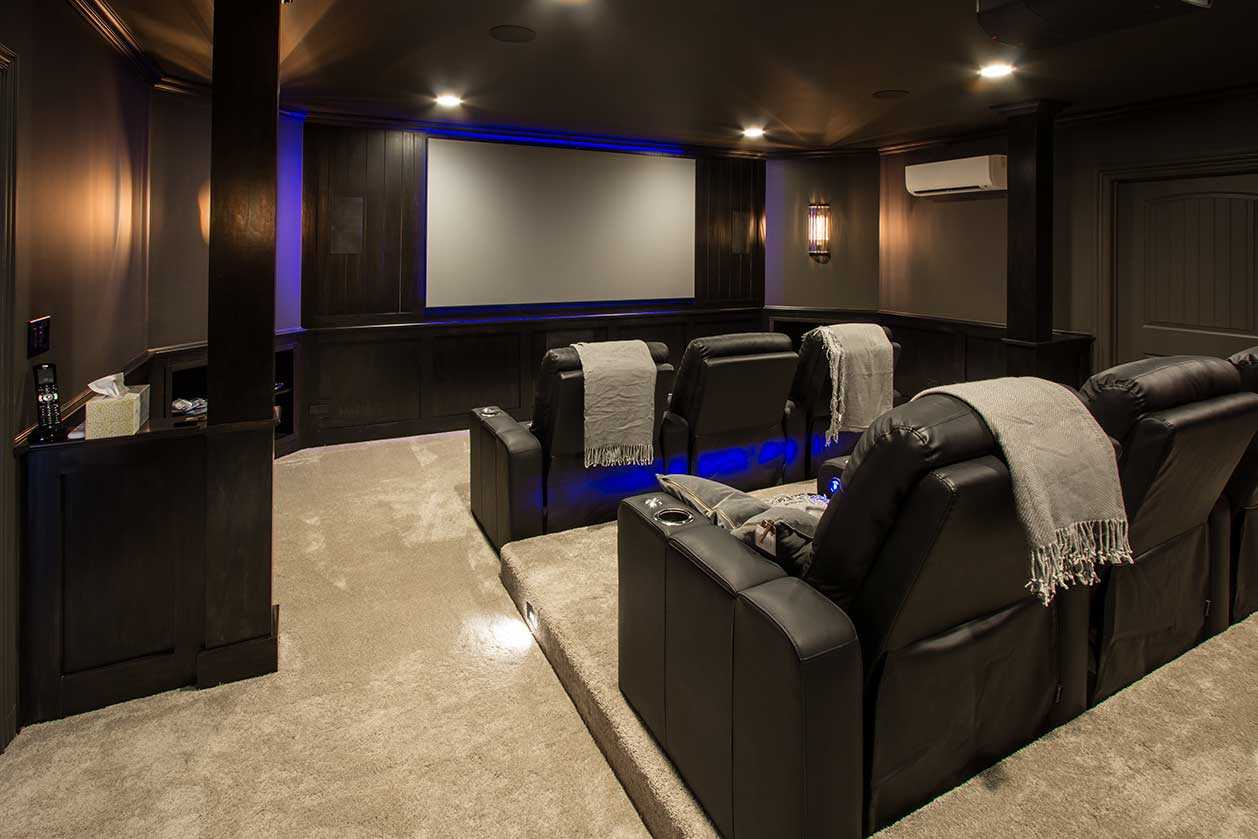 Basement remodeling movie theater with black lounge chairs
