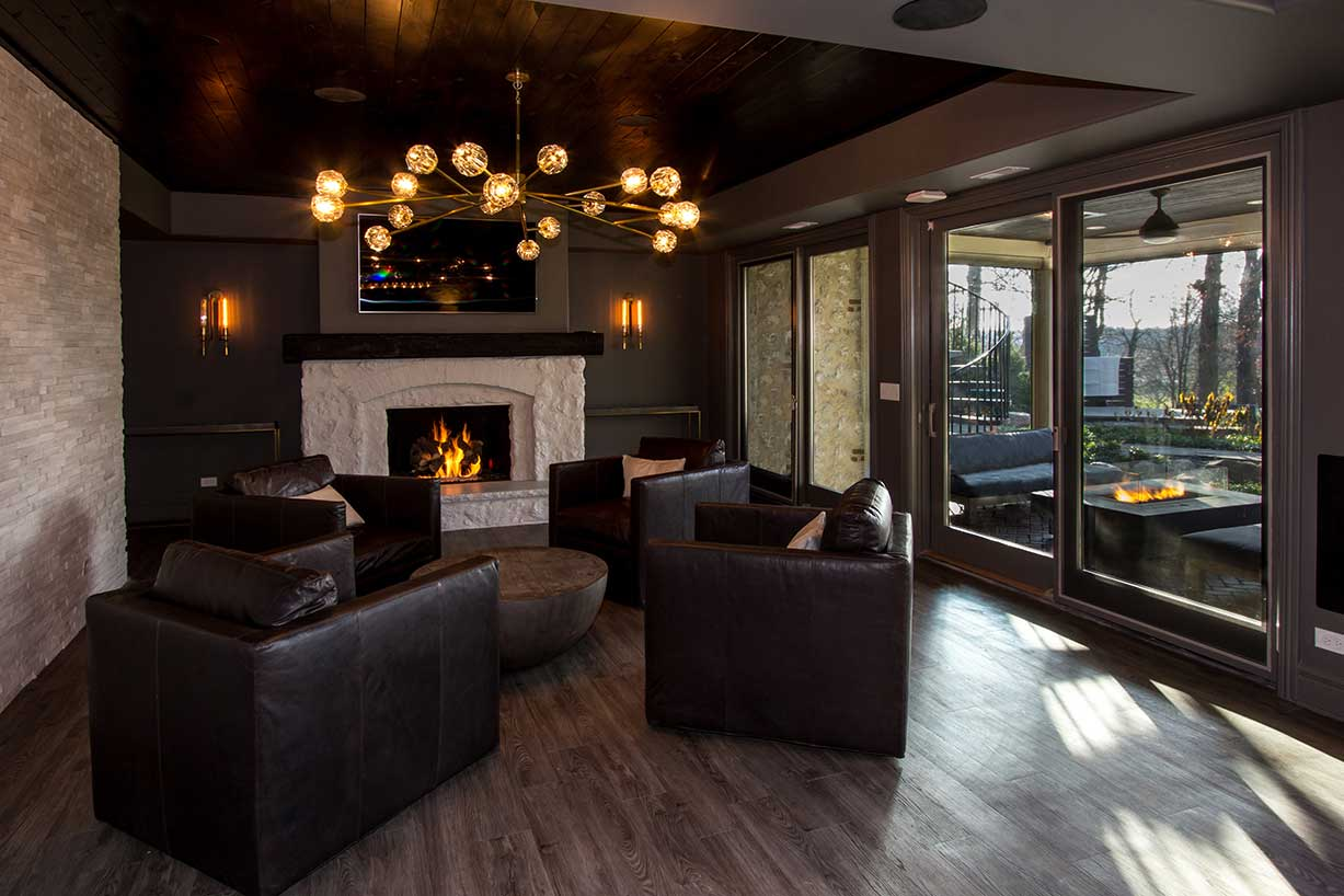 Stone fireplace with glass sliding door and black arm chairs