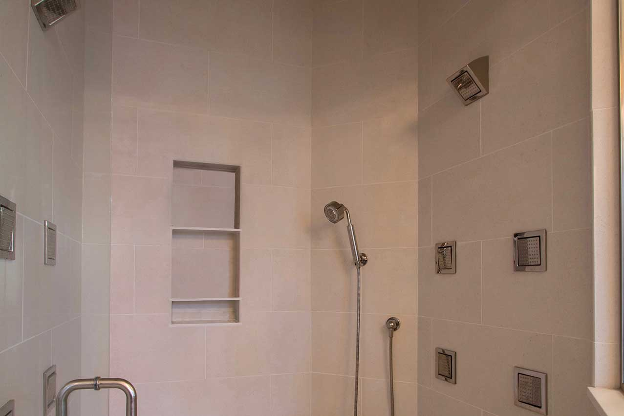 Interior of shower with off-white tile and glass door
