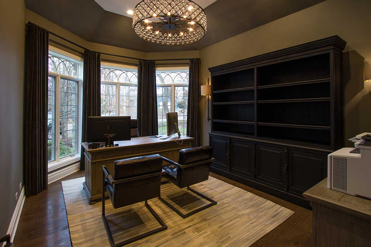 office with two chairs and desk in front of bay window