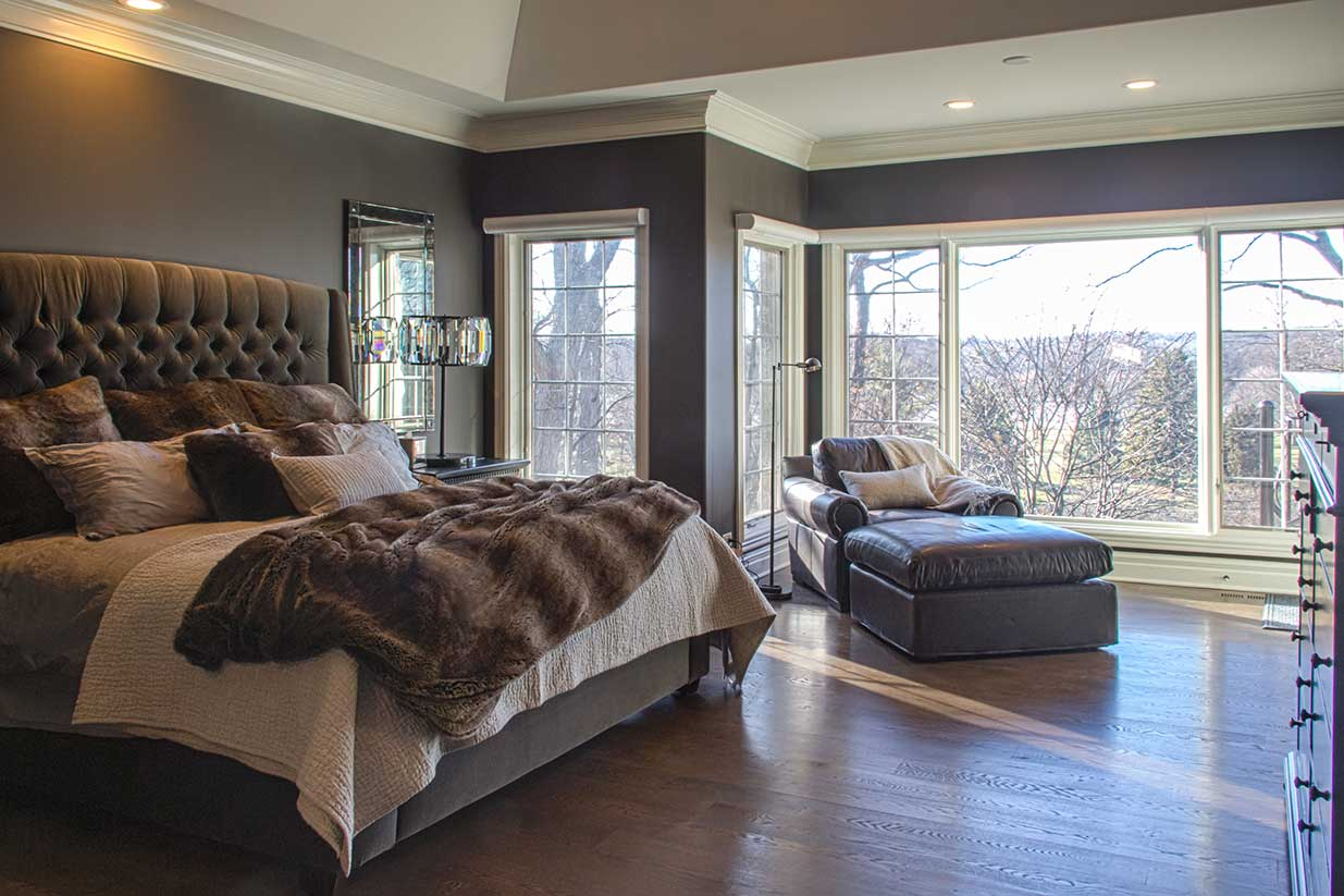 Large bed with chaise in front of large window