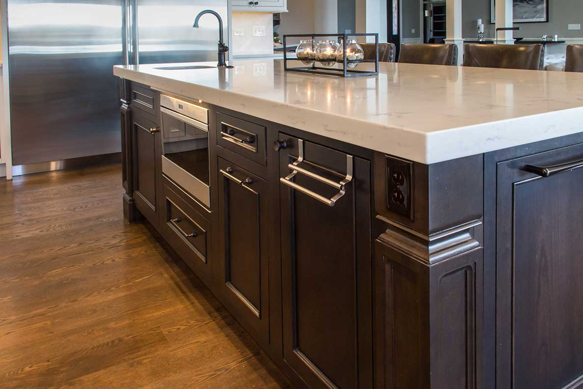 Brown wood island with marble counter top and built in oven