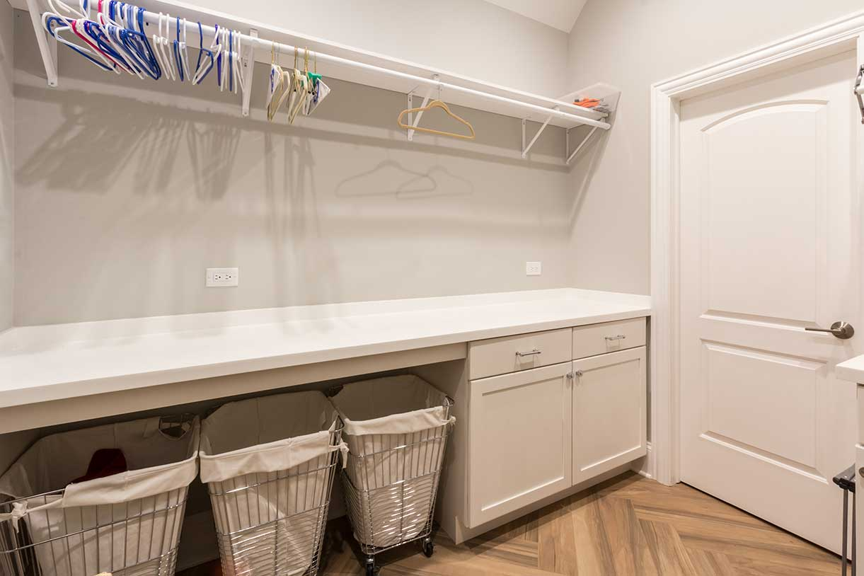 Closet with white counter and three hampers