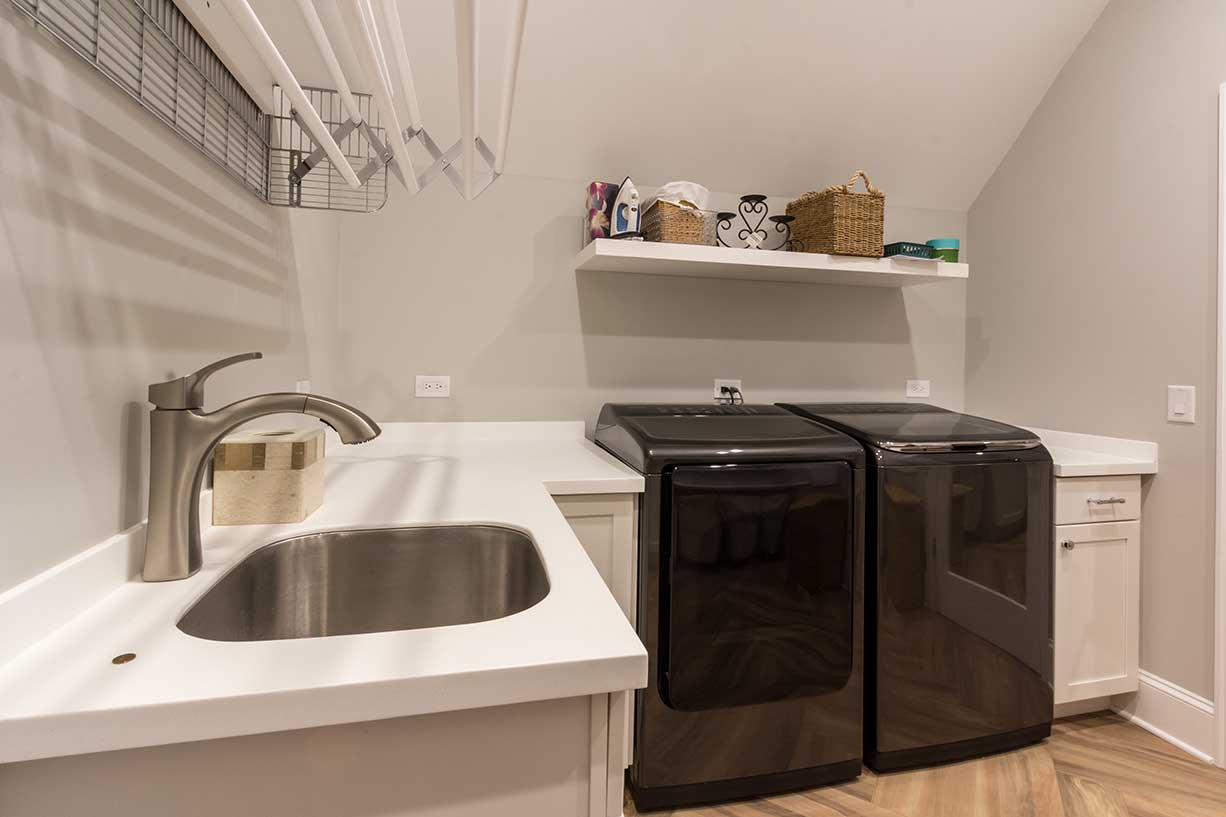 Laundry room with black washer and dryer and metal sink