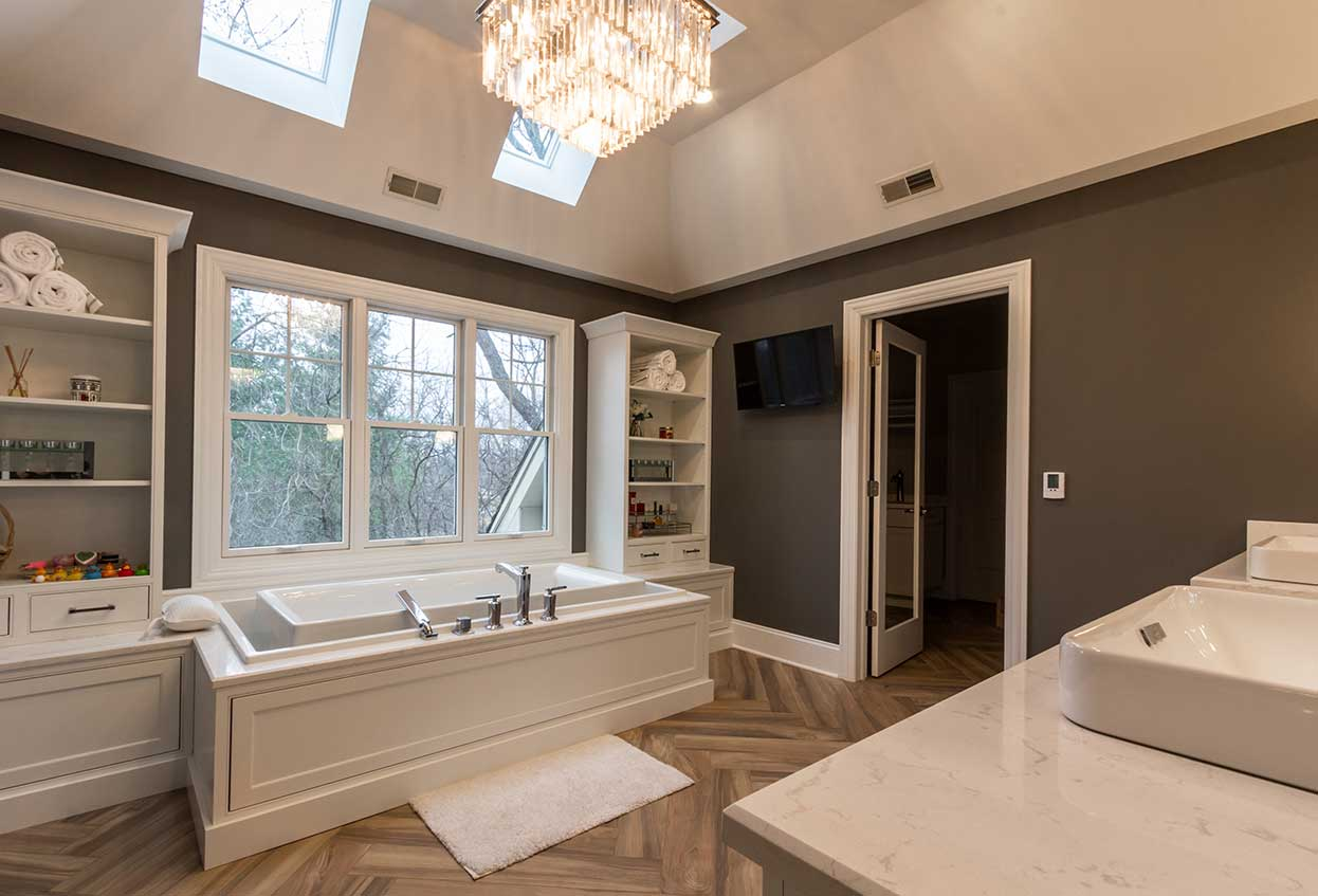 Tub with windows behind and white shelves on each side