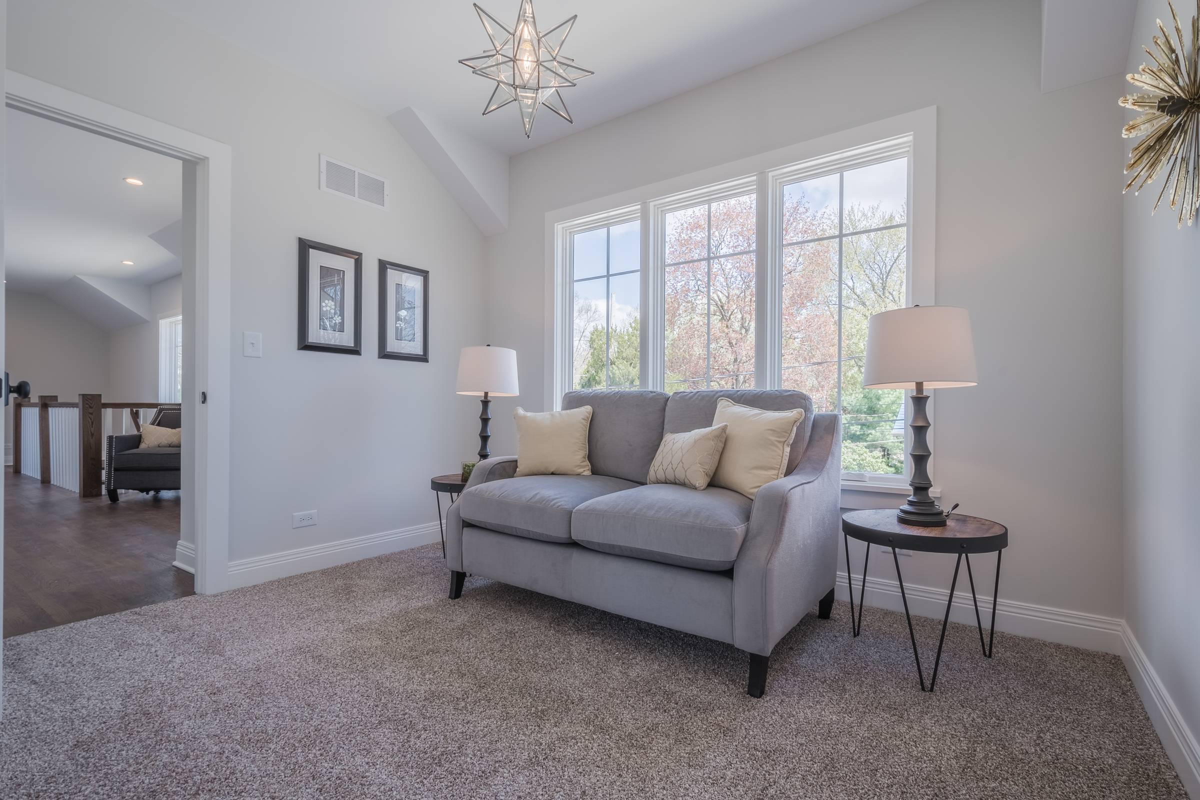 Love seat between two table lamps in front of window