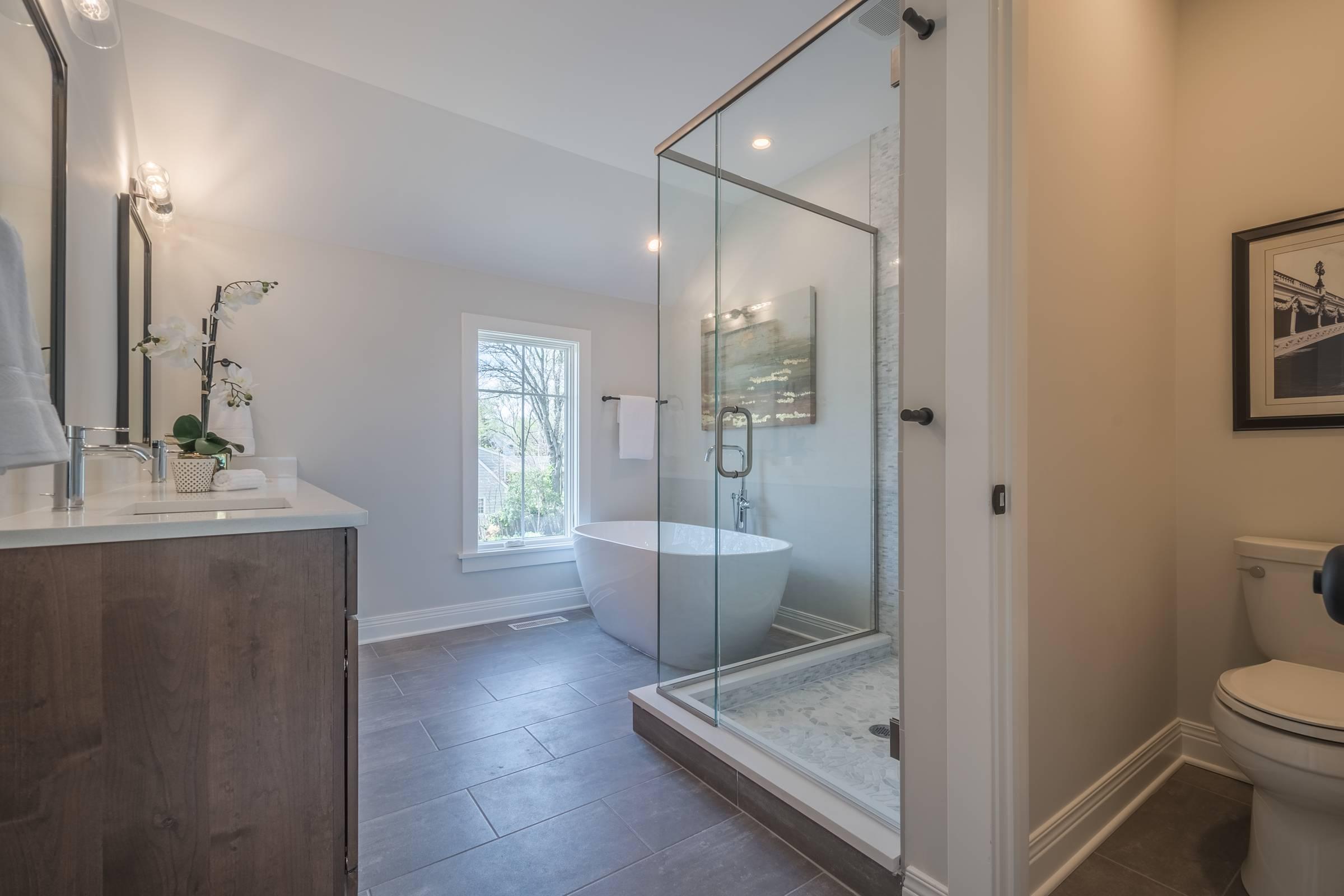 Shower with glass shower doors in front of ceramic tub