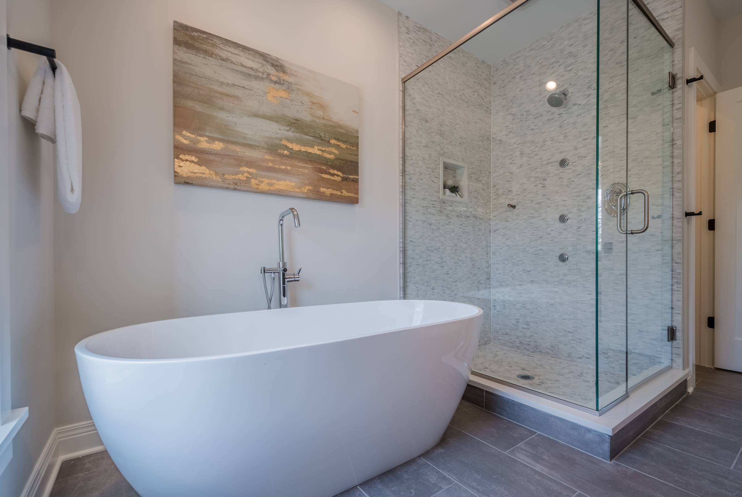 Ceramic tub next to glass shower with bronze painting