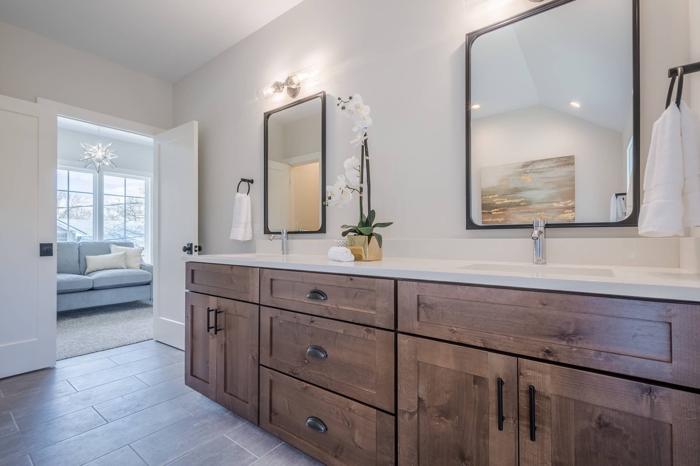 Bathroom with two mirrors over wooden cabinets with marble counters