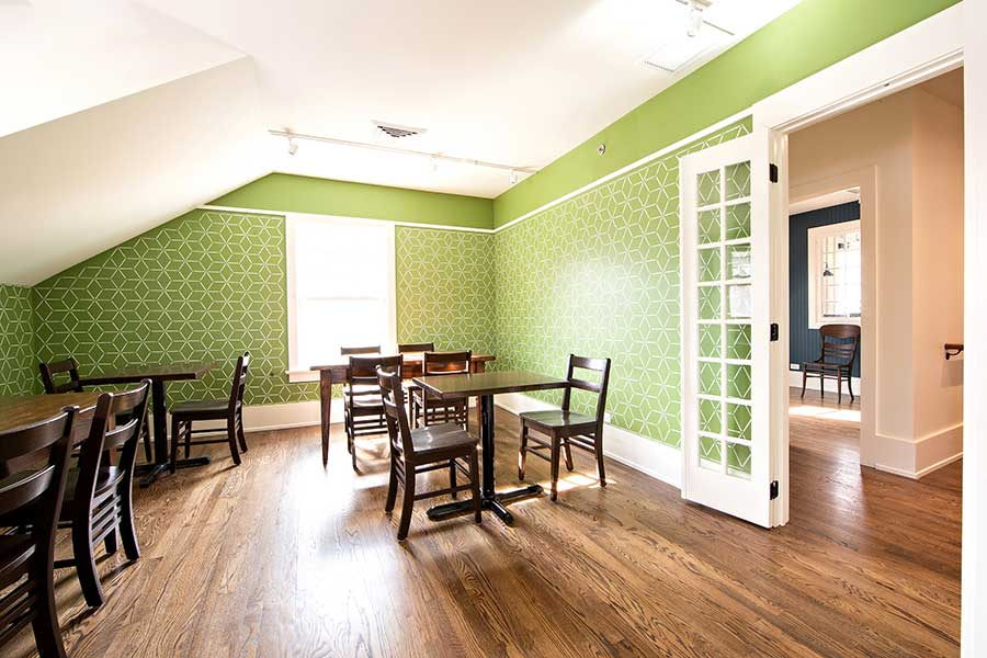 Dining tables with green wallpaper