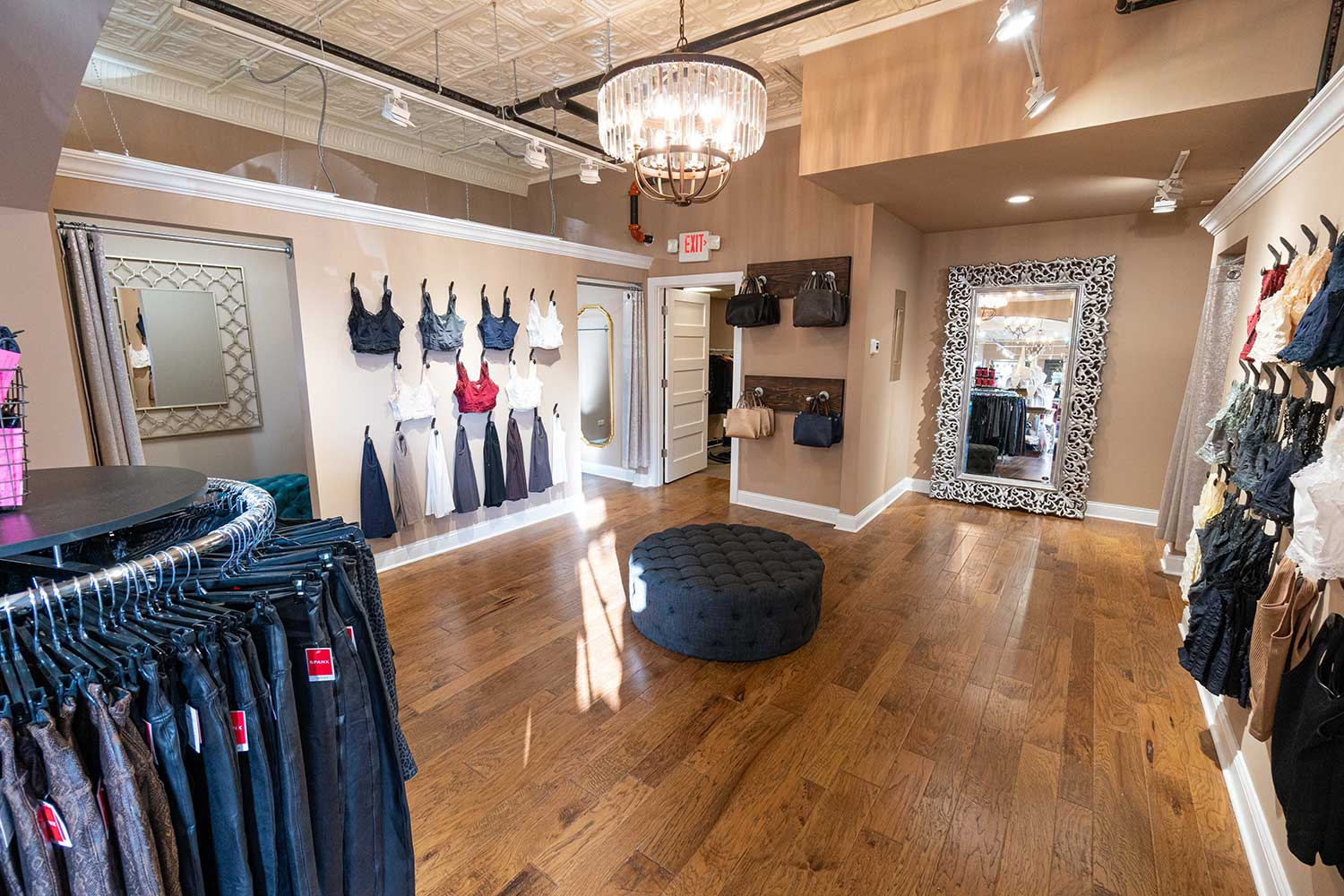 Changing room with clothes on the wall and chandelier