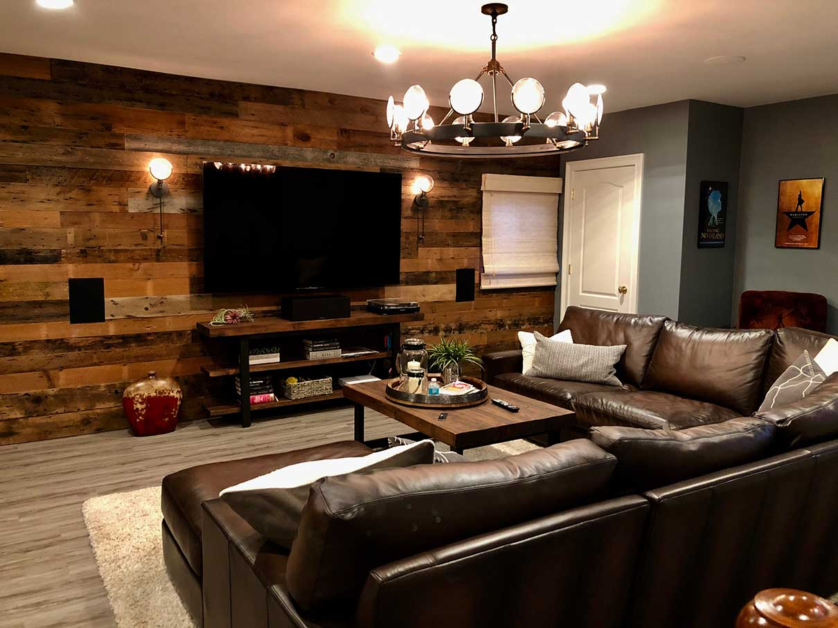 Living room with recycled barn wood wall and brown leather couch