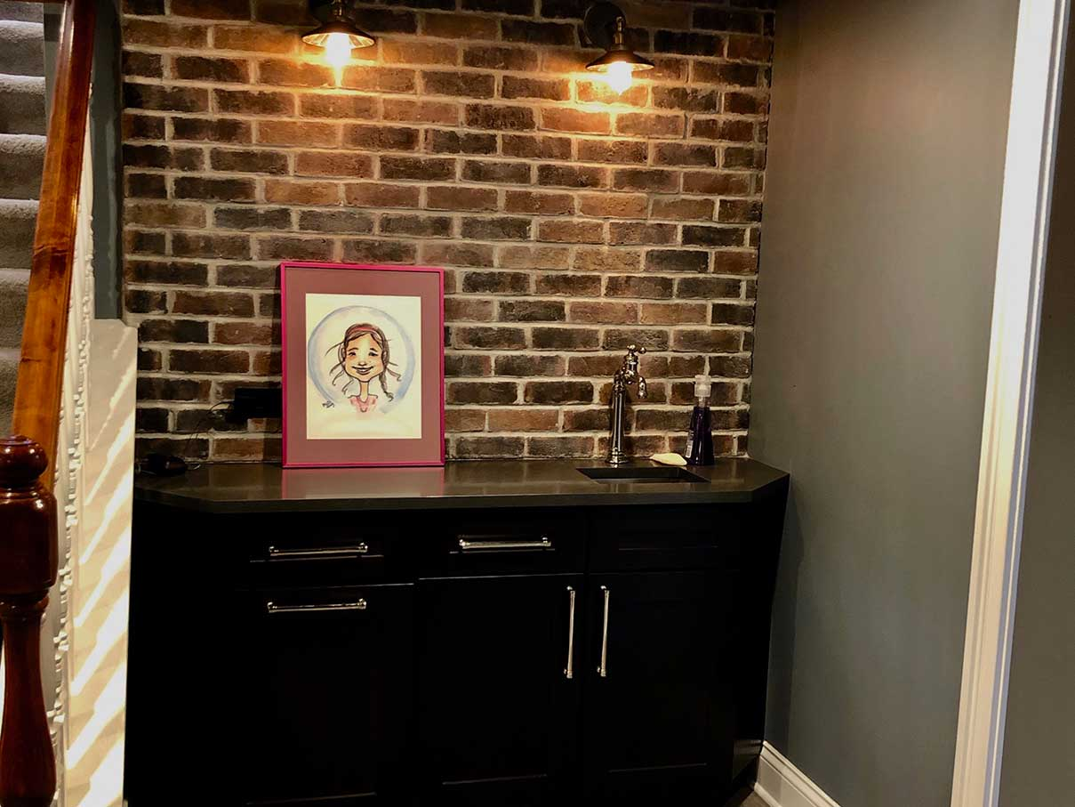Black cabinet with stone wall behind and picture on top