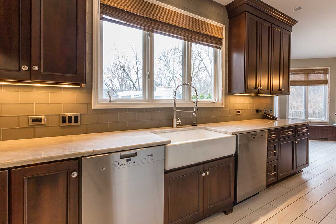 Kitchen sink with windows behind and brown cabinets bordering