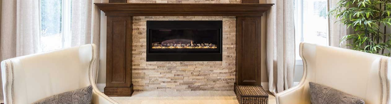 Stone fireplace with wooden mantle and white chairs