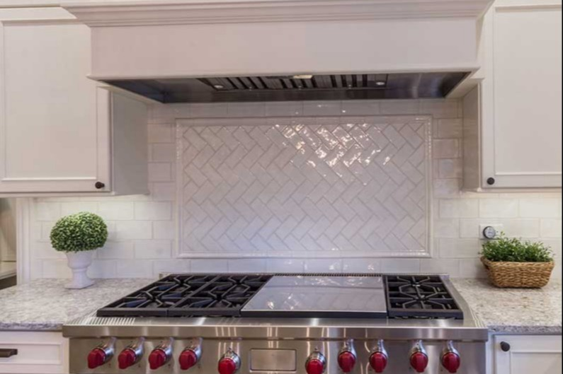 Stove top with red dials and white tile backsplash