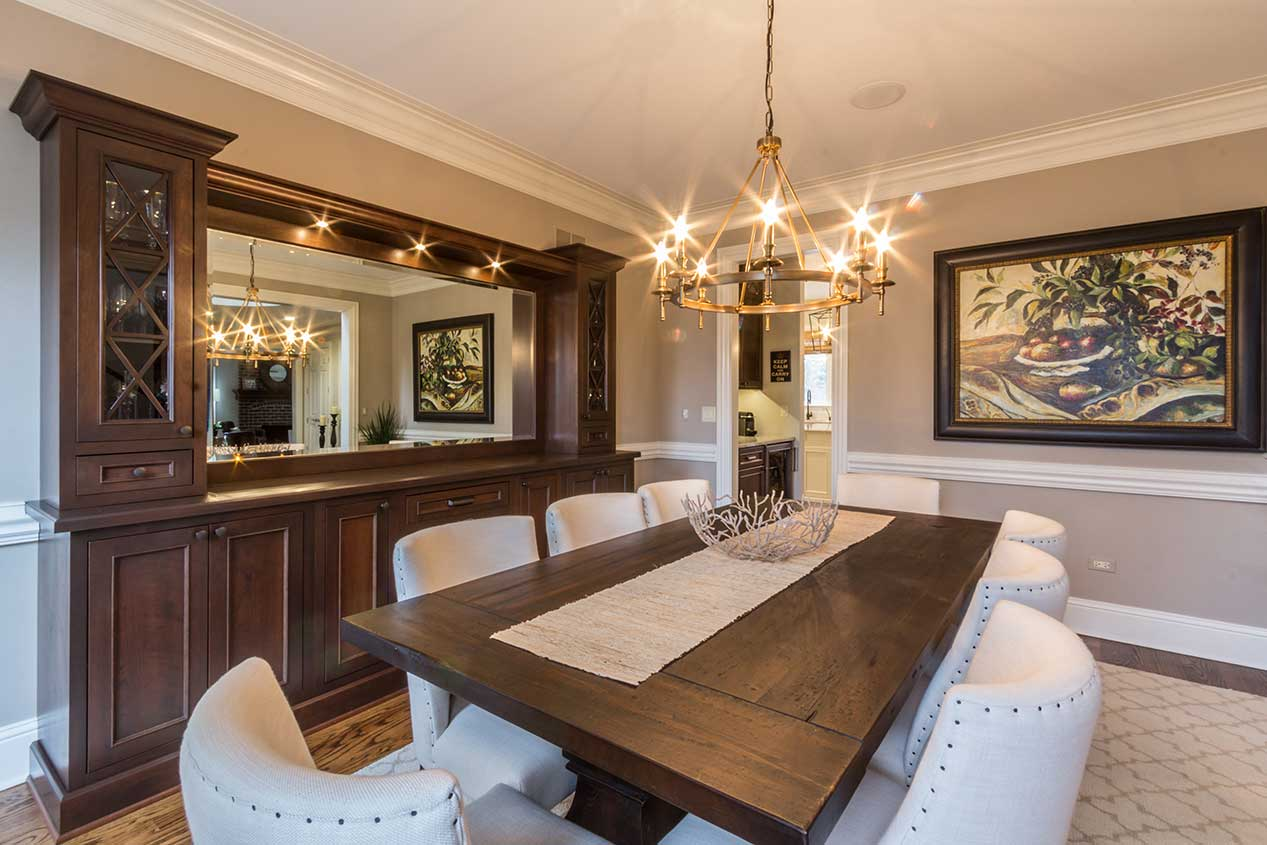 Dining room with white chairs and dark wood table and cabinets