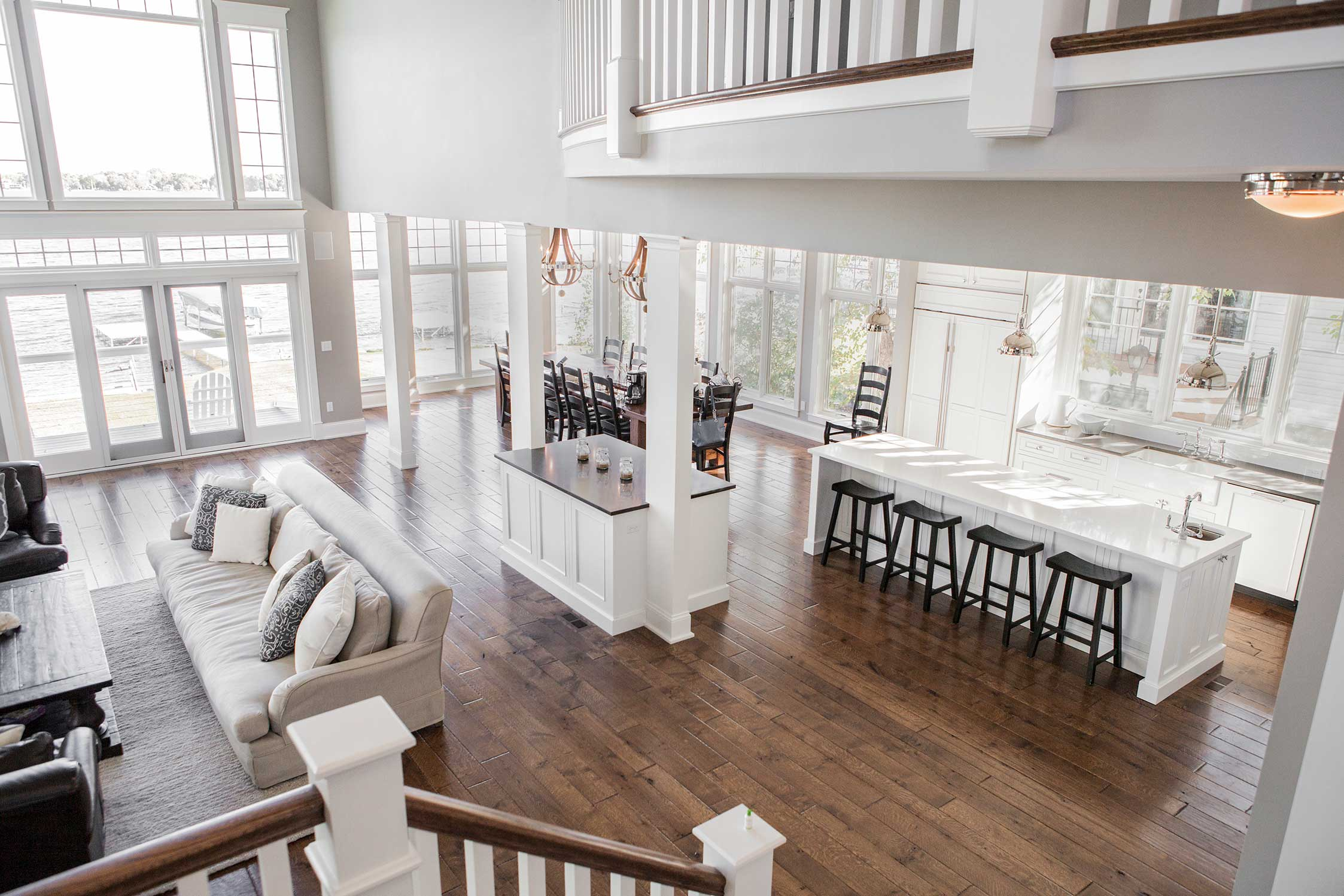 Banister view of living room, dining room, and kitchen