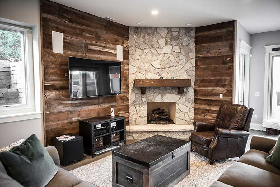 stone fireplace with wood border and sitting area with black TV