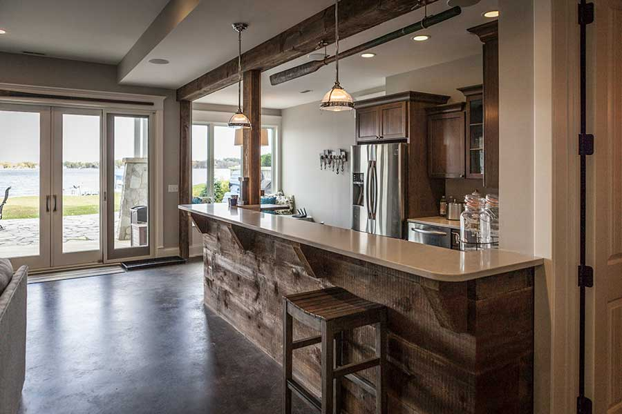 Basement bar with wood finishing and brown cabinets