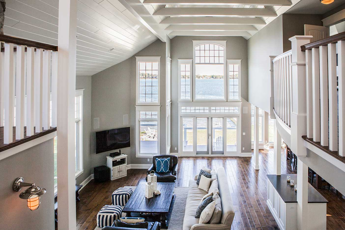 Living room view with furniture and large windows that show lake