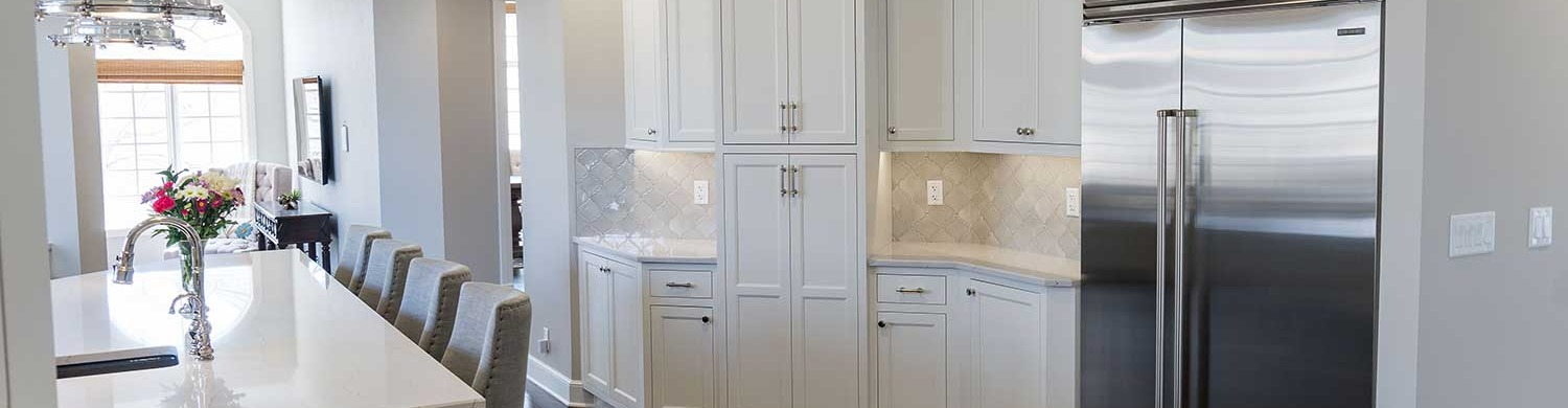 Kitchen island with white cabinets and metal fridge in background