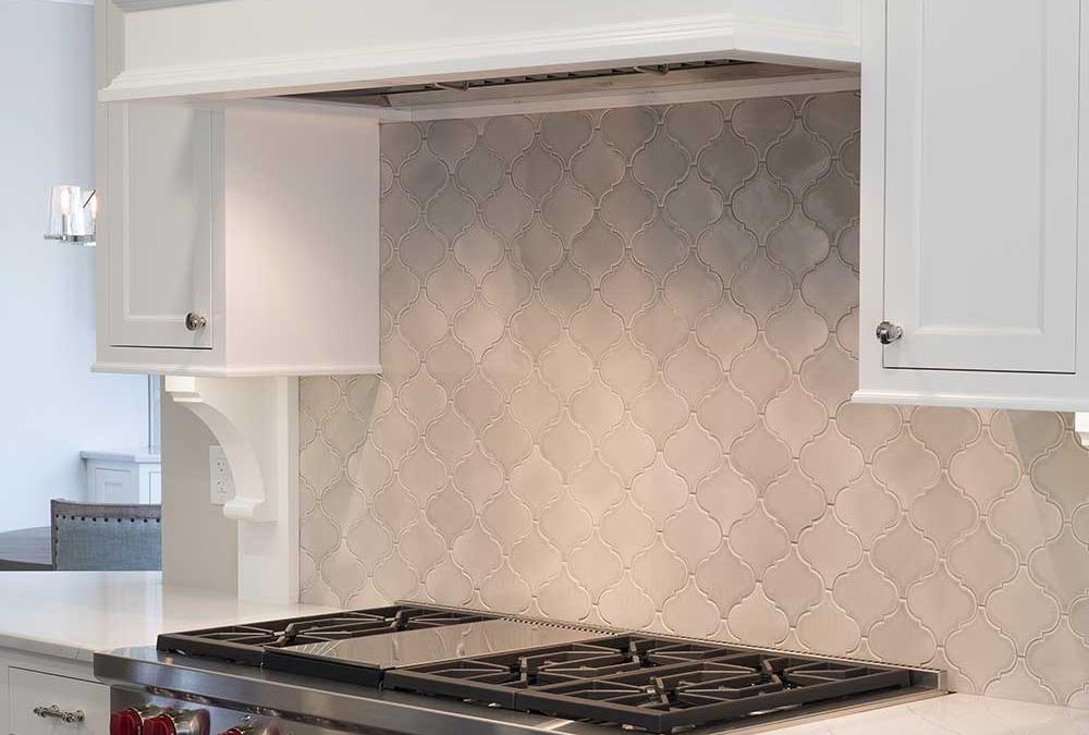 Tile backsplash behind stove top and white cabinets