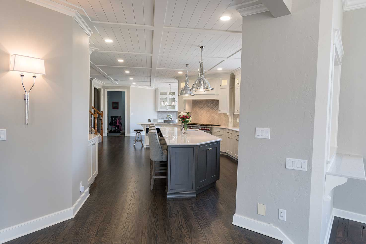 Full hallway view with marble counter and hanging lights