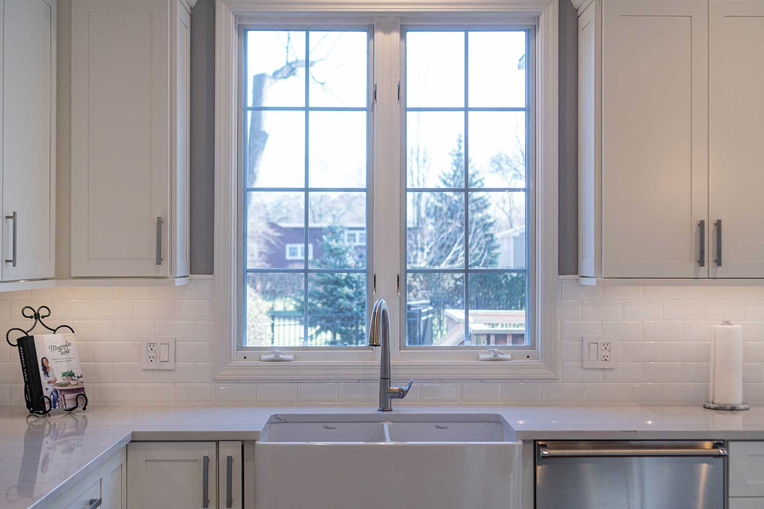 Kitchen sink with window behind and white cabinets