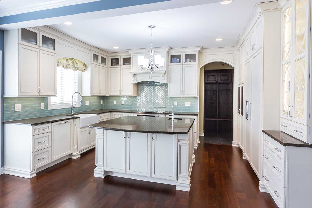 Full kitchen view of white cabinets and light green backsplashing