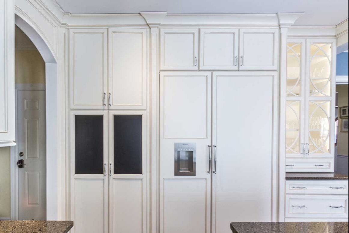 White cabinet storage area with complimentary white fridge and freezer