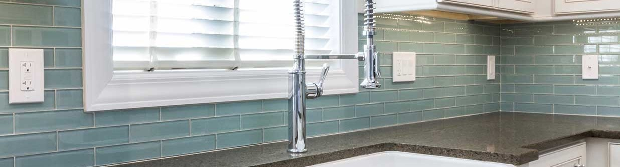 Closeup of kitchen faucet and tile backsplash