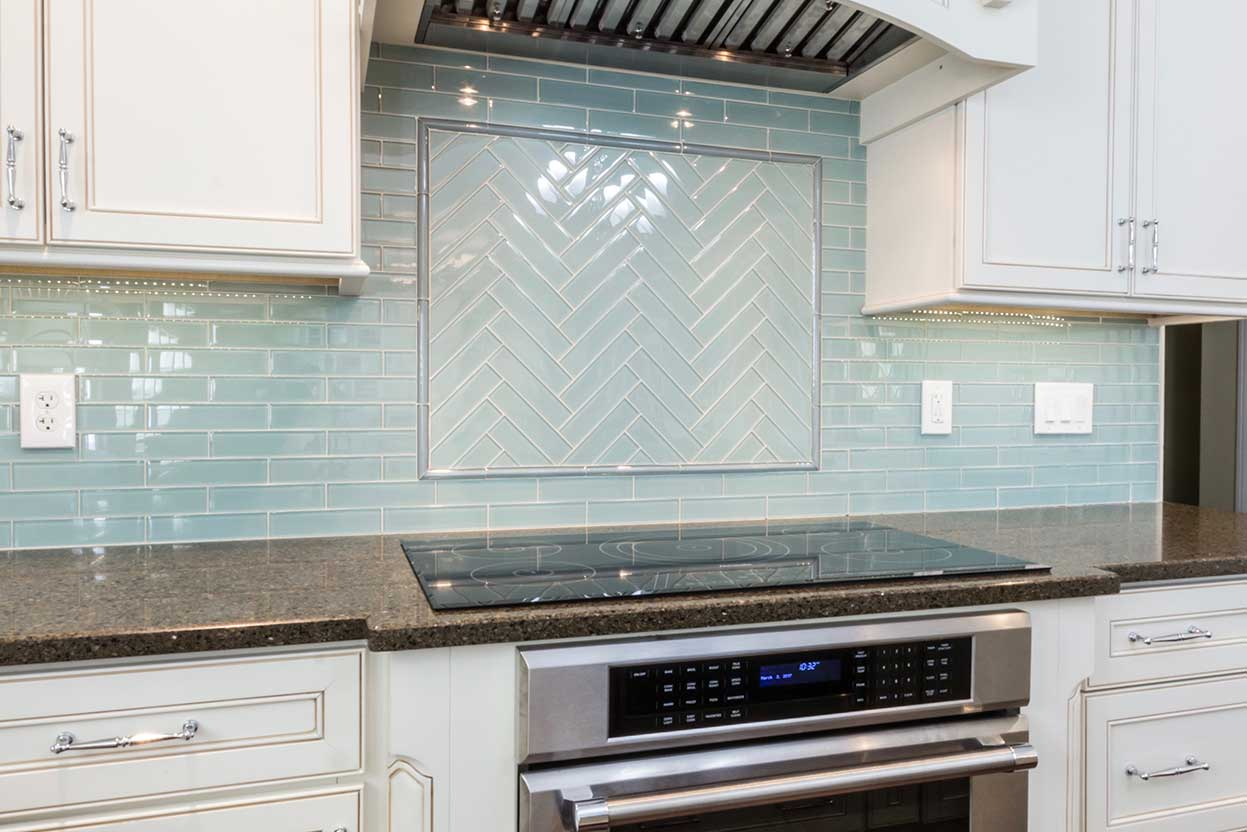 Closeup of stove with square diagonal backsplash motif