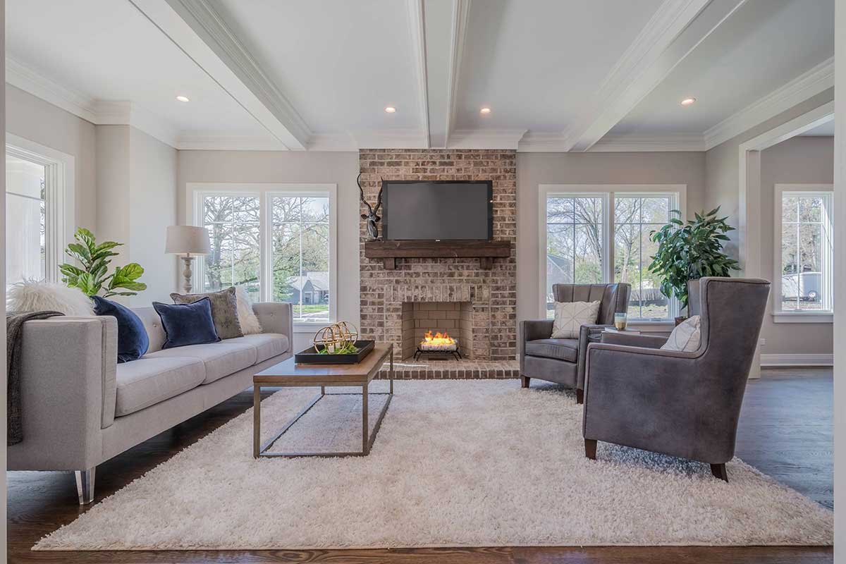 Living room with brick fireplace and furniture on white carpet