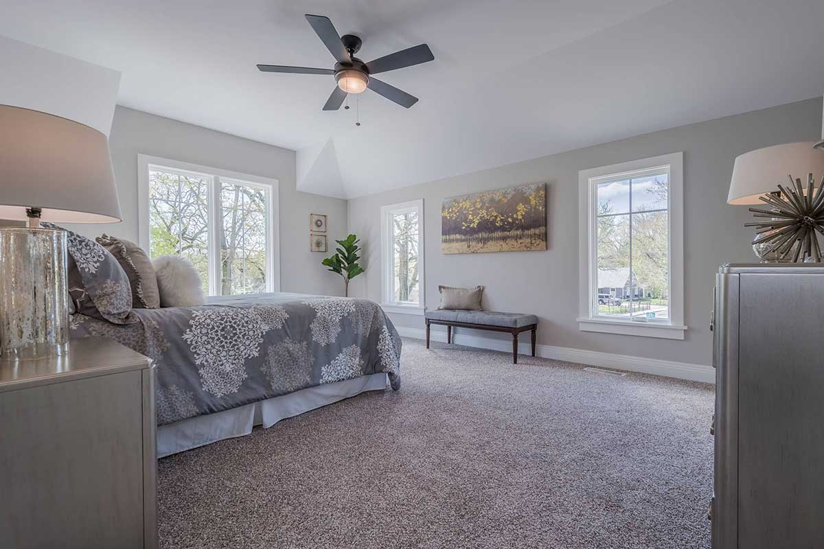 Bedroom with dark wood fan and grey sheets
