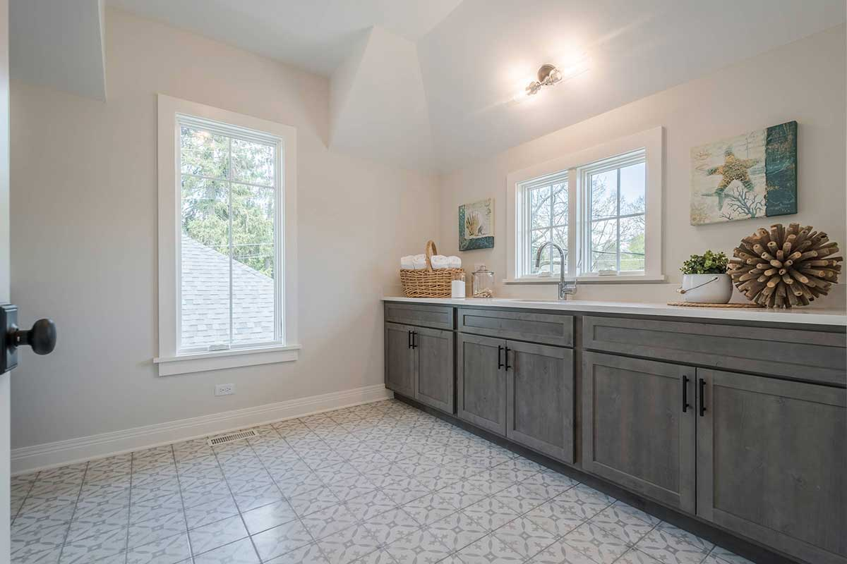 Bathroom with patterned tile floor and wooden cabinets
