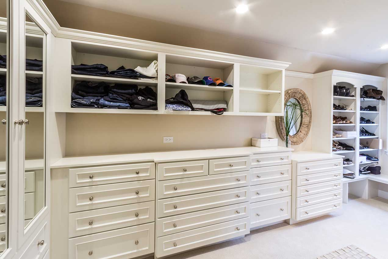 Closet with white drawers and shelves for additional storage