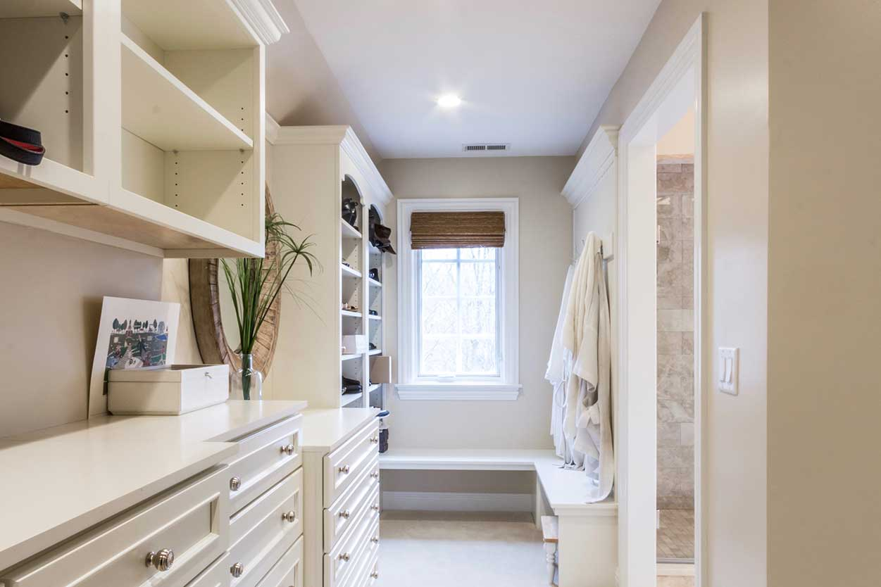 White cabinets and shelves on left wall, and shower door on right