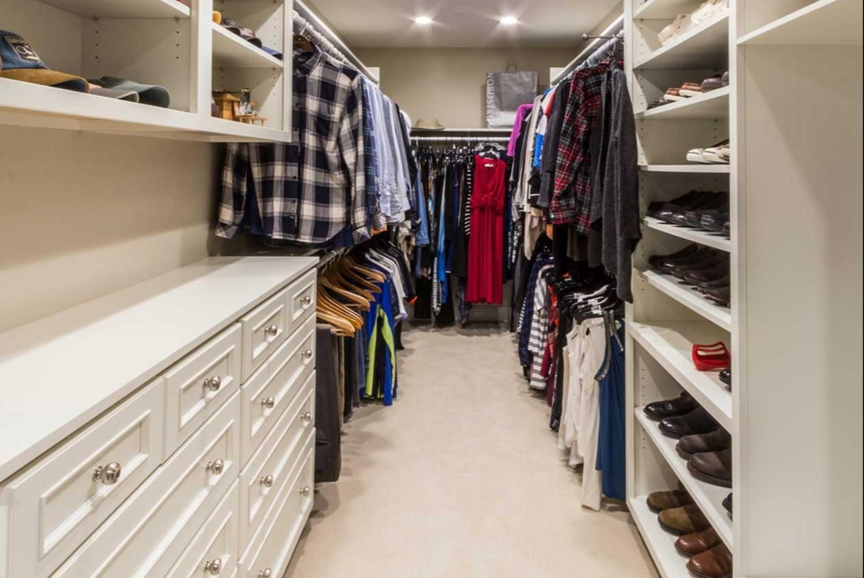Open closet with hanging clothes and shoes