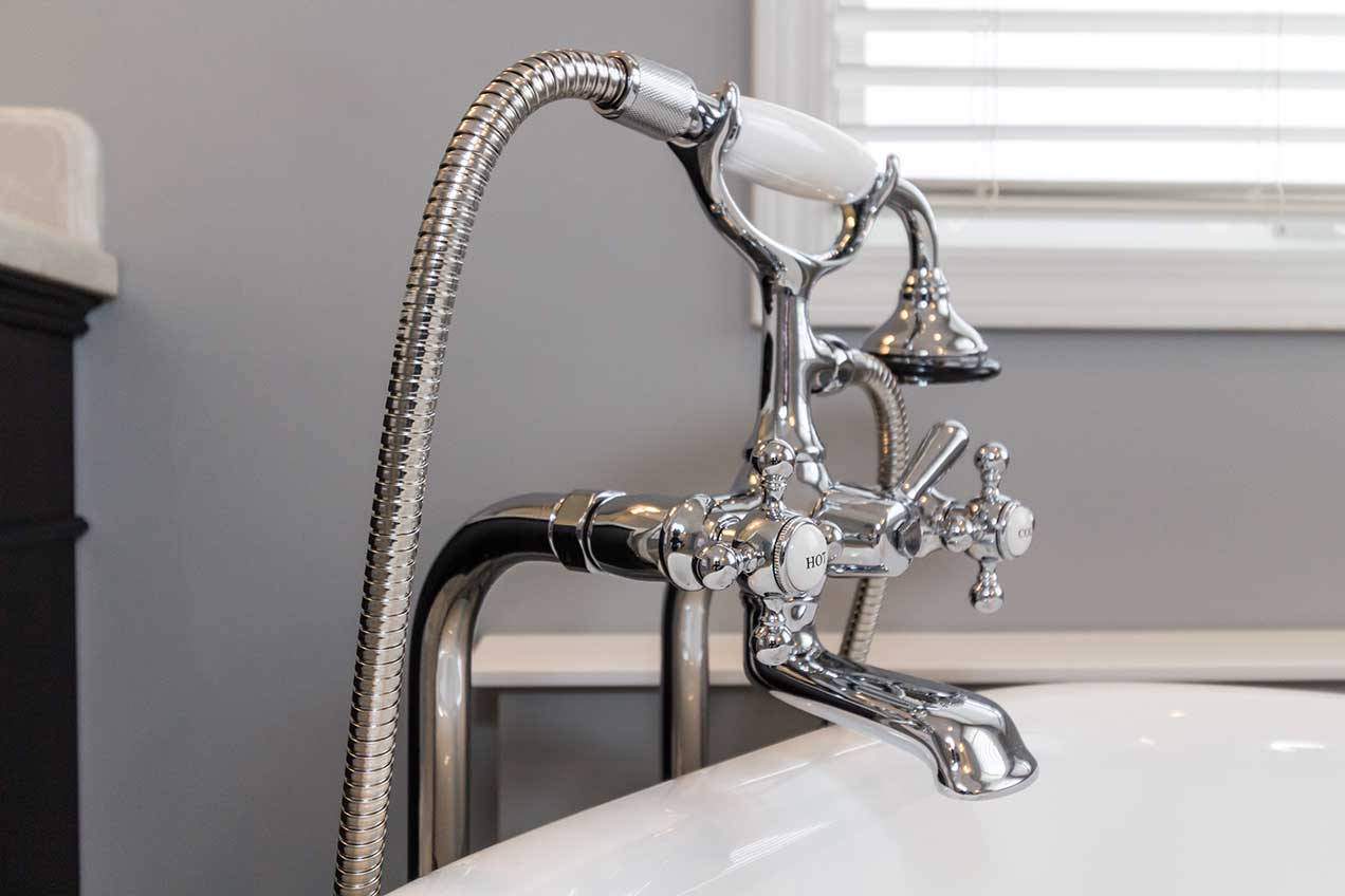 Silver ornate faucet head with white hot and cold labels