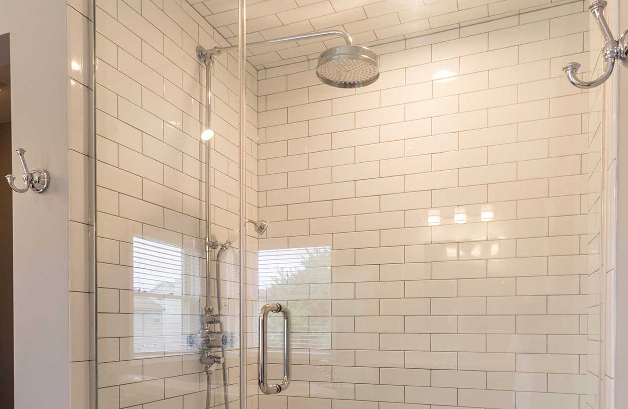 Softly lit shower with glass doors and tile