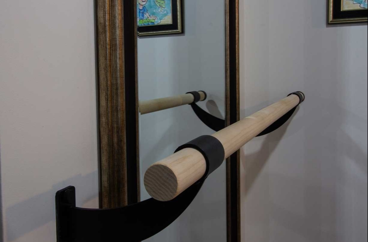 Mirror with bar for dance practice mounted to wall