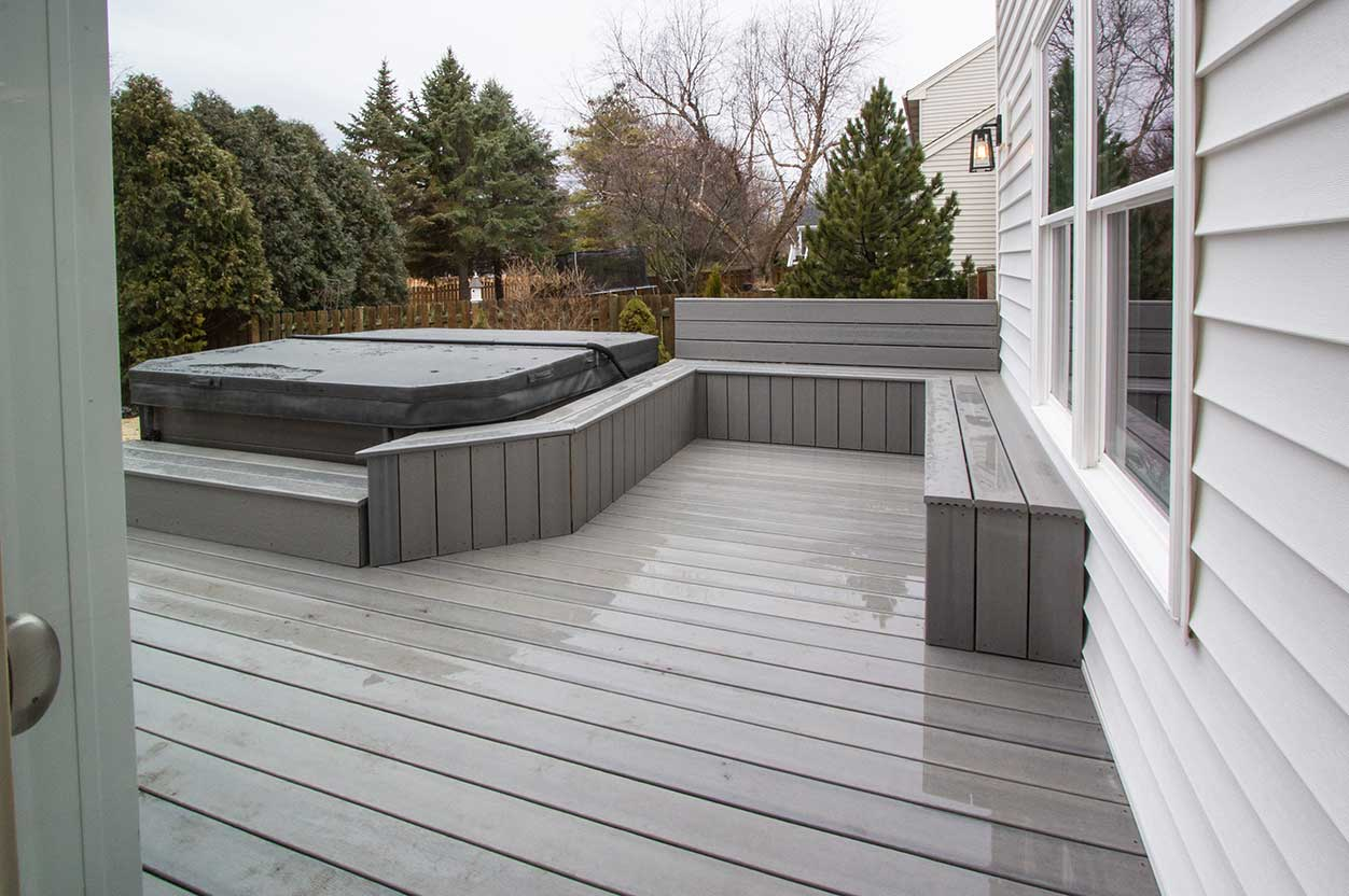 Grey deck with covered hot tub after rain