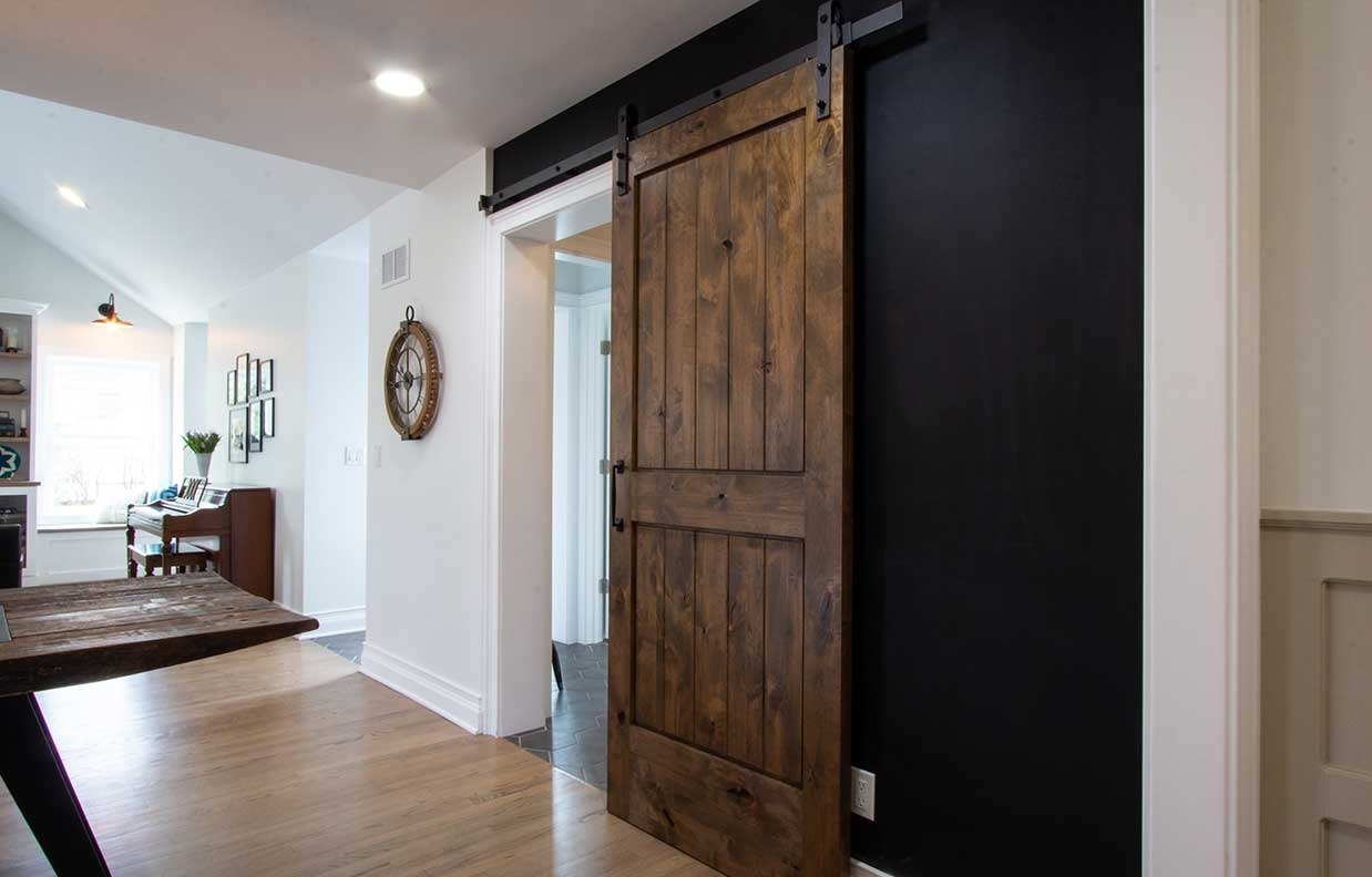 Brown wooden sliding door leading to basement staircase