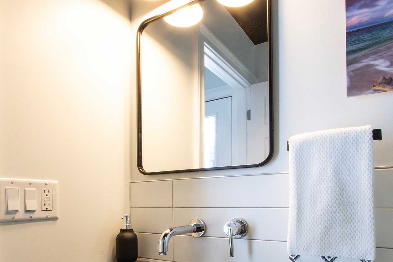 Mirror with white towel and faucets