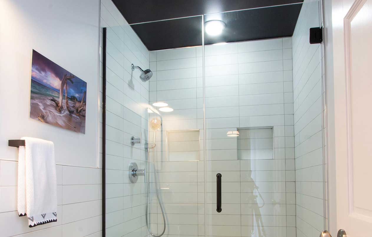 Glass shower door with bright light in center of ceiling